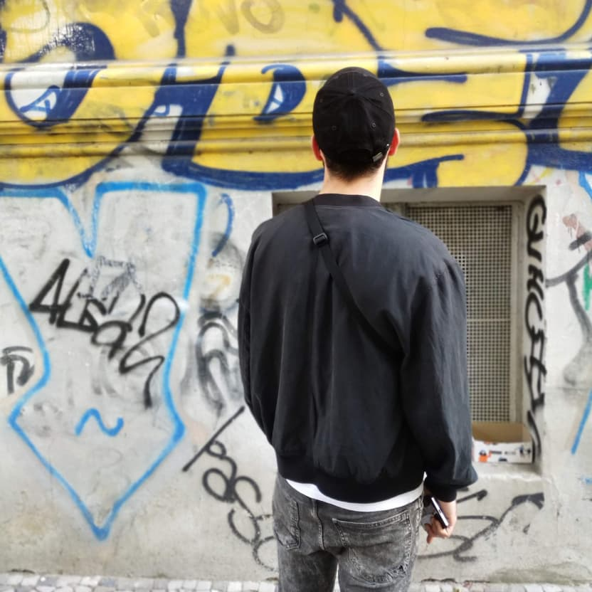 A young guy looking at a wall full of graffiti